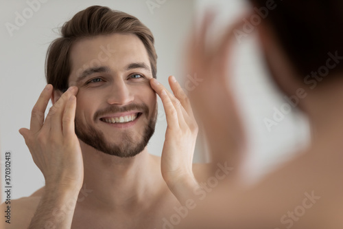 Leinwand Poster Close up mirror reflection smiling satisfied young man touching skin under eyes,