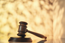 Judge (auction) Gavel On Table With Abstract Background