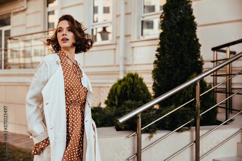 Fototapeta Amazing girl in long white coat looking away