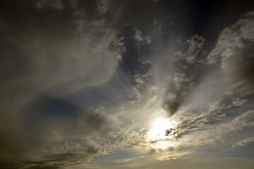 Panorama of the cloudy sky, including the solar disk and light cirrostratus clouds, shaped like a cross. A fine spring day in the Western Urals.
