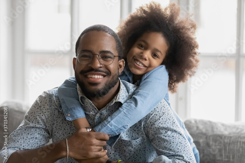 Obraz Portrait of cute little ethnic girl hug smiling african American young father show love and affection, happy biracial dad and small daughter hug cuddle, enjoy tender close family weekend together - fototapety do salonu