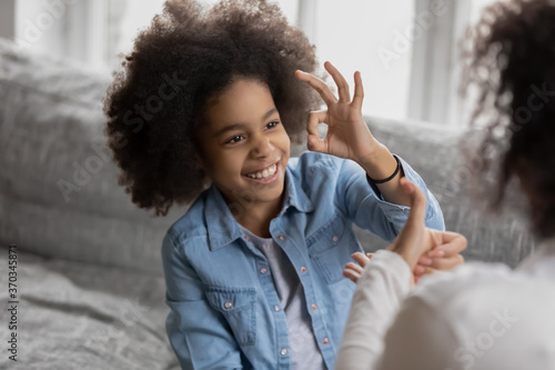 Obraz na plátne Smiling small african American deaf disabled girl show gesture with hand practic