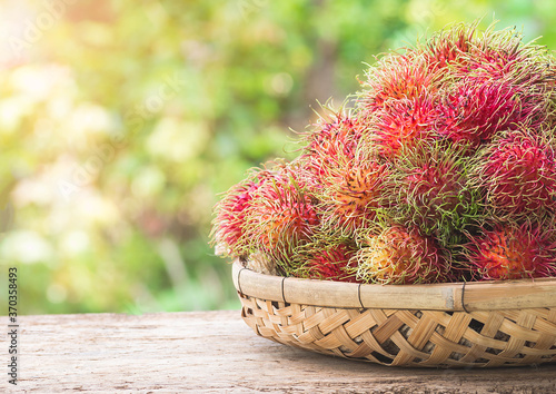 Fresh rambutan in basket on wood with blur image background for tropical fruit in thailand Poster Mural XXL