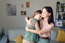 Young Loving Mother Embracing Her Cute Affectionate Daughter In Home Environment