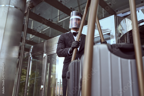 Obraz Hotel worker in protective equipment operating a heavy trolley - fototapety do salonu