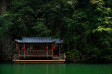 A Small Chinese Style Wooden House In The Forest By The Lake.