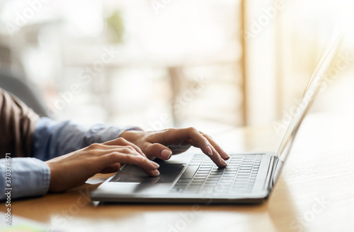 Obraz Female hands typing on laptop over blurred background - fototapety do salonu