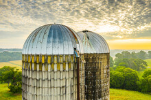 Two Silos And A Bird At Sunrise