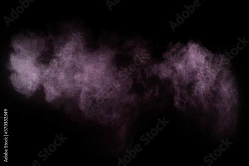Purple powder explosion on black background. Colored powder cloud. Colorful dust explode. Paint Holi..