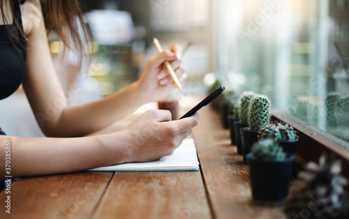 Fotografiet Close-up, young asian woman using mobile phone working on wooden counter in cafe