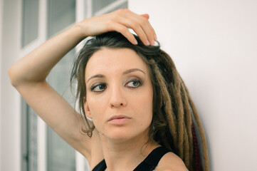 Indoors female portrait of a woman with dreadlocks hairstyle and smoky eyes makeup