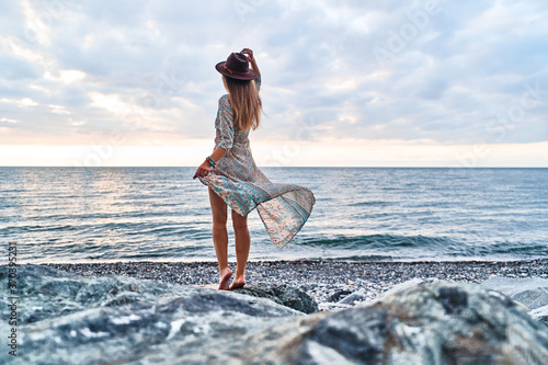 Boho chic woman in long fluttering dress and felt hat standing back on stone by Fototapete
