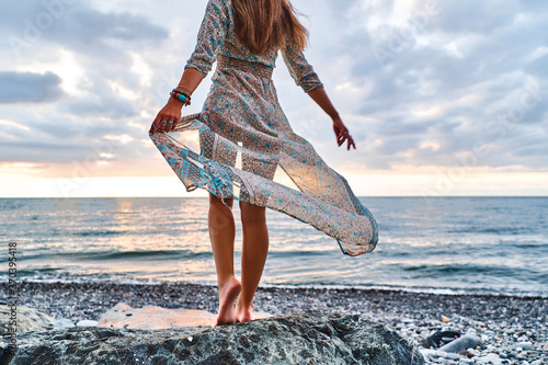 Boho woman with long legs and waving dress standing on a stone by the seashore a Canvas