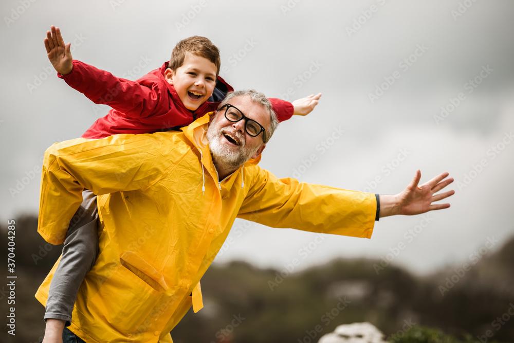 Fototapeta Father giving son piggyback ride outdoors