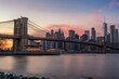 Colorful Pink Sunset Behind The Brooklyn Bridge and New York Skyline