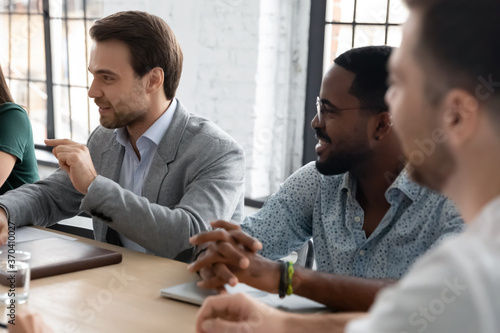 Close up diverse employees discussing project at corporate meeting, business partners sitting at table in boardroom, colleagues coworkers sharing ideas, brainstorming, mentor training staff