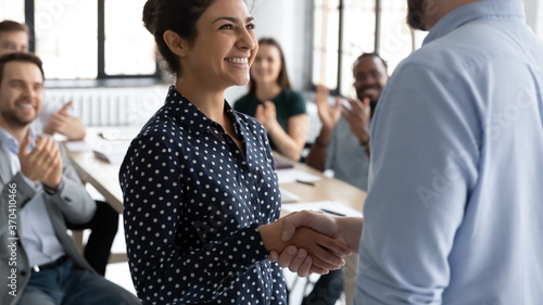 Close up executive shaking smiling Indian businesswoman hand at meeting, diverse Wallpaper Mural