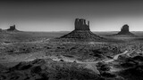 Black and White Photo showing the gravel road winding around East and West Mitten Buttes in the desert landscape in Monument Valley Navajo Tribal Park in southern Utah, United States