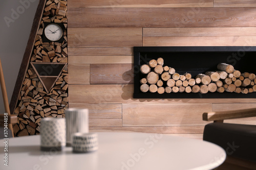 Decorative fireplace with stacked wood in cozy living room interior Fototapet