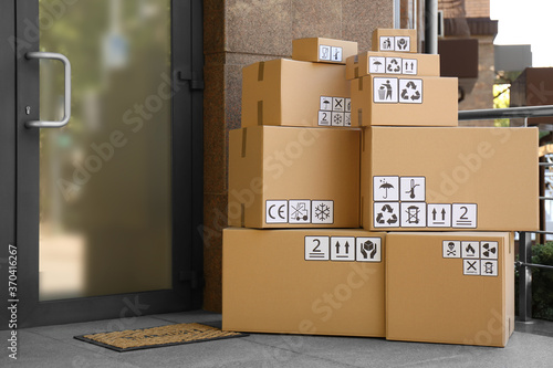 Fotografía Cardboard boxes with different packaging symbols on porch near entrance