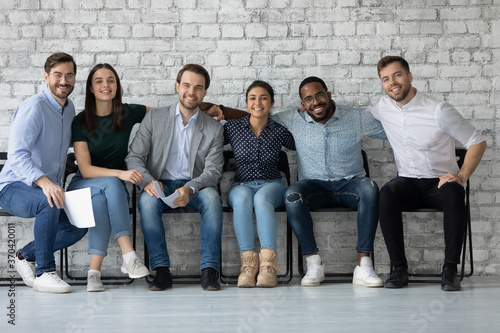 Obraz Portrait smiling diverse candidates business people hugging, siting in row in queue, successful confident applicants interns waiting for job interview, recruitment and hiring concept - fototapety do salonu
