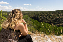 Thoughtful Blonde Girl With Her Back, Looking At The Horizon With A Leafy Background Of Trees
