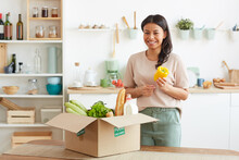 Waist Up Portrait Of Beautiful Mixed-race Woman Smiling At Camera While Enjoying Food Delivery Service Standing By Box Of Vegetables In Kitchen, Copy Space