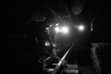 Silhouette Of A Working Miner In A Mine