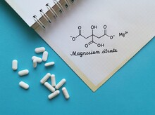 Structural Chemical Formula Of Magnesium Citrate Molecule With White Pills. Magnesium Citrate Is A Magnesium Preparation In Salt Form With Citric Acid, It Is Used Medicinally As A Saline Laxative.