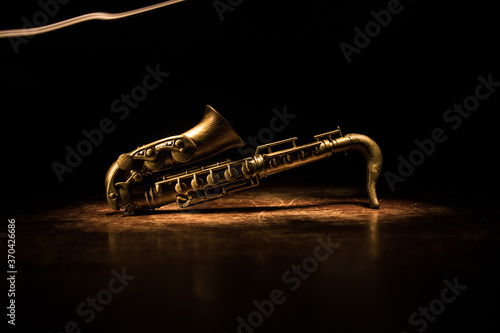 Fotografie, Obraz Alto gold sax miniature with colorful toned light on foggy background