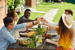 Multi-ethnic group of friends clinking cocktail glasses while enjoying outdoor dinner in Summer, copy space