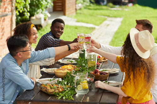 Multi-ethnic group of friends clinking cocktail glasses while enjoying outdoor d Fotobehang