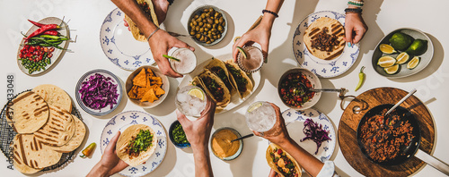 Obraz Friends having Mexican Taco dinner. Flat-lay of beef tacos, tomato salsa, tortillas, beer, snacks and peoples hands clinking glasses over white table, top view. Mexican cuisine, comfort food concept - fototapety do salonu