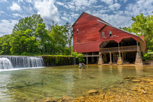 An Old Red Mill And A Dam.
