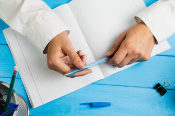 A schoolgirl sits at a desk holding a pen on a blue background.