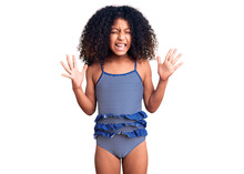 African American Child With Curly Hair Wearing Swimwear Celebrating Mad And Crazy For Success With Arms Raised And Closed Eyes Screaming Excited. Winner Concept