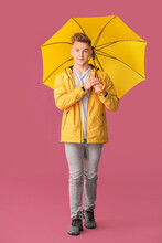 Young Man With Umbrella On Color Background