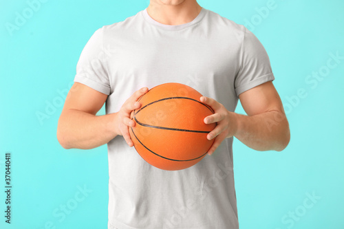 Young man with ball on color background