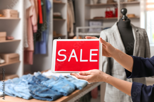 Obraz Female seller holding board with text SALE in modern clothes store - fototapety do salonu