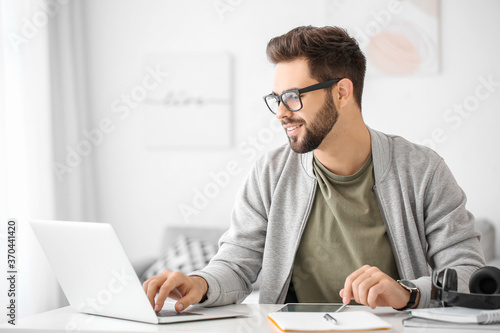 Obraz Young man using laptop for online learning at home - fototapety do salonu