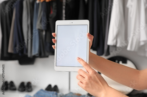 Obraz Woman with tablet computer in modern clothes store - fototapety do salonu