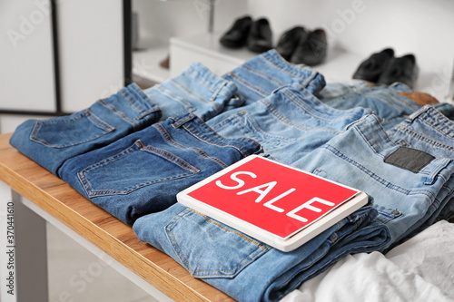 Obraz Table with stylish clothes in modern store - fototapety do salonu