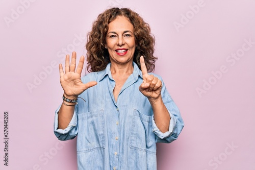 Middle age beautiful woman wearing casual denim shirt standing over pink background showing and pointing up with fingers number six while smiling confident and happy Billede på lærred