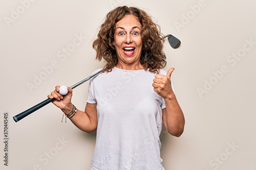 Middle age beautiful sportswoman playing golf using stick and ball over white ba Fototapete
