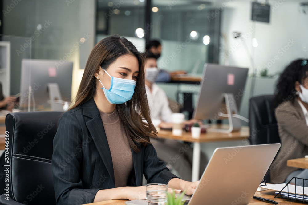 Fototapeta Asian young businesswoman wearing mask working on computer in office.