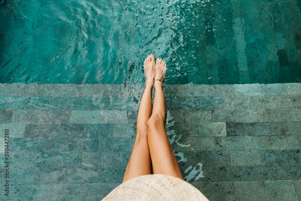 Fototapeta Closeup of beautiful female legs in water of a pool summer concept
