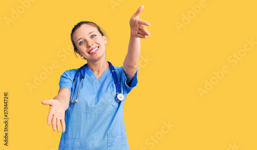 Fotografie, Obraz Young beautiful blonde woman wearing doctor uniform and stethoscope looking at the camera smiling with open arms for hug