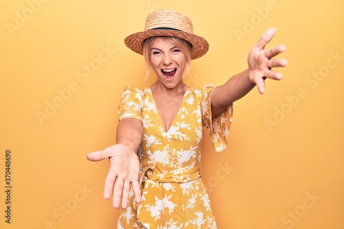 Fotografie, Obraz Beautiful blonde woman on vacation wearing summer hat and dress over yellow background looking at the camera smiling with open arms for hug