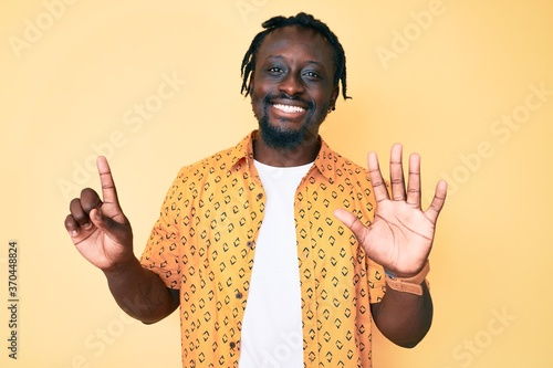 Young african american man with braids wearing casual clothes showing and pointing up with fingers number six while smiling confident and happy.