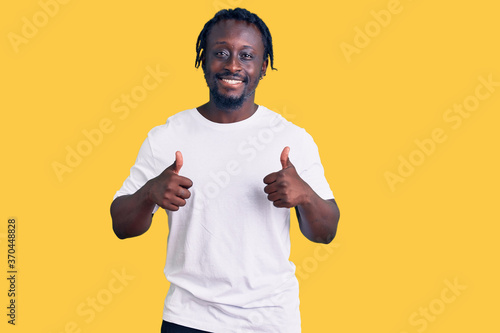 Young african american man with braids wearing casual white tshirt success sign doing positive gesture with hand, thumbs up smiling and happy. cheerful expression and winner gesture.